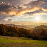 Village on hillside behind forest in mountain at sunset Stock Photography