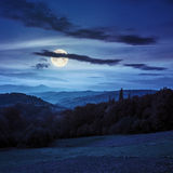 Village on hillside behind forest in mountainl at night Stock Photography