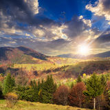 Village on hillside meadow with forest in mountain at sunset Stock Photography