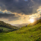 Village on hillside meadow with forest in mountain at sunset Stock Images
