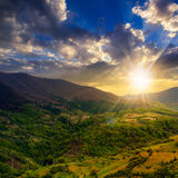 Village on hillside meadow with forest in mountain at sunset Royalty Free Stock Photos