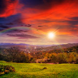 Village on hillside meadow with forest in mountain at sunset. Autumn landscape. village on the hillside. forest on the mountain light fall on clearing on Royalty Free Stock Photos