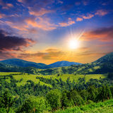 Village on hillside meadow with forest in mountain at sunset Royalty Free Stock Photo
