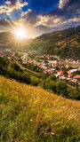 Village on hillside meadow with forest in mountain at susnet Royalty Free Stock Photos
