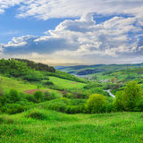 Village on hillside meadow with forest Stock Photos