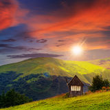 Village on hillside meadow with forest at sunset Stock Image