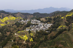 Village, on a hillside yellow rape and winding mountain path Royalty Free Stock Image