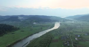 Village on a hilly area on the river bank. Village on a hilly area on the shallow freshwater river bank, which grows green spruce and other trees and grass stock footage