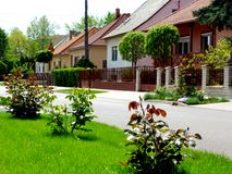 Village homes along a friendly green street with lush front yards. And well kept lawns, little gardens, rose bushes and new red clay roofs. home ownership stock photography