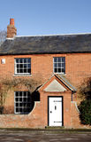 Village House. Red Bricked English Village House with matching front wall and entrance Royalty Free Stock Images