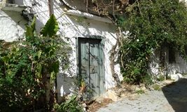 Village house. Old village house. Fodele. Crete. Greece. White-washed stone walls. Green wood door Stock Photography