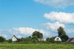 Village house roofs under blue summer sky Stock Photos
