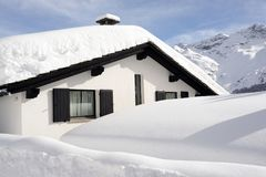 A village house in the snow covered hill in the alps switzerland in winter.  Royalty Free Stock Photography