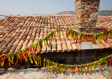 Village house with tile roof pile and red chilly peppers hanging on the wall. Typical house of rural Turkey. Stock Photo