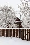 Village house under snow behind  wooden fence Stock Images