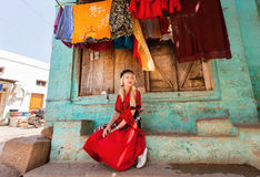 Village house and young woman sitting at front of colorful building in small indian town. Royalty Free Stock Photos