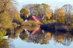 Village houses near river. Autumn trees water boat Royalty Free Stock Photography