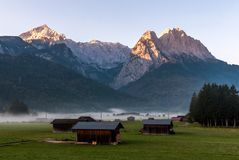 Village huts on foggy mountain meadow. In the Alps with rocks in the background Stock Images