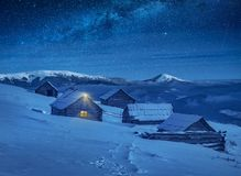 Village illuminated by moon light with wooden houses at winter royalty free stock photography