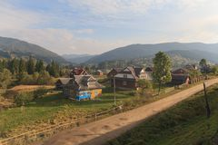Village is illuminated by the sun and the mountains are far away. Carpathians. Ukraine Stock Photos