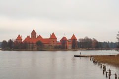 Village of Karaites, Lithuania, Europe. Lithuanian landmark in late autumn. Girl standing on the pier and taking photos on her pho. The view to lake and Trakai Royalty Free Stock Photos
