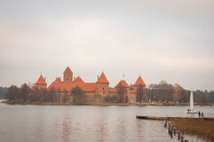 Village of Karaites, Lithuania, Europe. Lithuanian landmark in late autumn. The view to pier and yacht sailing at lake near Trakai. The view to pier and yacht Stock Images