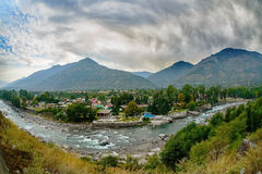 Village in Kullu Valley, Beas river foreground Stock Photo