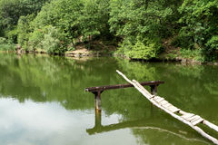 Village lake. Low-quality platform for swimming on the shore of Forest Lake Stock Photography