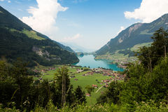 Village by the lake. Small village by a brilliant blue lake nestled in the Swiss Alps Royalty Free Stock Photography