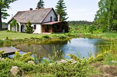 Pastoral rural house in northern Poland. Village landscape, pastoral rural house with barbeque area, northern Poland. Outdoor architecture. Pond reflection stock photography