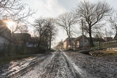 Village landscape, swamp and wet road, old houses and trees around, countryside path, road theme, Western Ukraine. Village landscape, swamp and wet road, old Royalty Free Stock Images