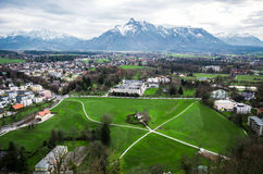 Village with lawn and Alps range background Royalty Free Stock Image