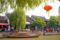 Village life on the banks of the canal, Zhujiajiao, China. Village life on the banks of the canal. People walk along the canal with a traditional boat docked on royalty free stock photo
