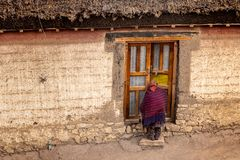 Village life, Spiti, Tibetan, himachal. Old lady entering a Traditional Tibetan house in a Village in Spiti valley, Himachal Pradesh. This area will be covered royalty free stock photo