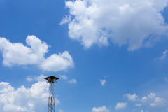 Village local broadcast tower on the blue sky background. Royalty Free Stock Photo