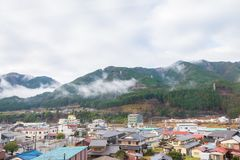 Village is located in front of the mountain and the view of the mist on the mountain. The village is located in front of the mountain and the view of the mist on stock images