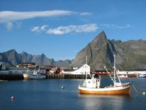 Village on the Lofoten Islands. Boat and village on the Lofoten Islands in Norway Stock Photo