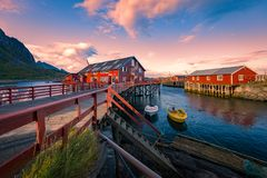 Village on Lofoten islands in Norway, Europe. Village of Reine on Lofoten islands in Norway. Traditional red wooden houses and mountains. Sunset sky with clouds Stock Photo