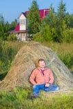 Village man near the haystack Royalty Free Stock Photography