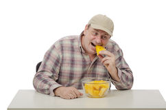 Village man tries a yellow watermelon. Village man in a plaid shirt tries a yellow watermelon Stock Photography