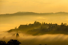 Village in the mist. An early morning photo of a village in south of Poland near Zakopane. Mist and fog surrounds a village with a church at its heart Stock Photo