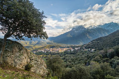 Village of Moltifao in Corsica with snow covered mountains behin. Village of Moltifao in Corsica with the snow capped mountains in the distance and rocks and Royalty Free Stock Photos