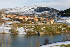 Village of mountain snow on the slope of a reservoir in winter. Town farm with snow in winter: Alba de los Cardaños beside the reservoir of Camporredondo in stock image