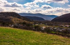Village in mountainous rural are. Beautiful countryside landscape in springtime. Cloudy afternoon in Carpathians Stock Image