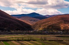 Village in mountainous rural are. Beautiful countryside landscape in springtime. Cloudy afternoon in Carpathians Royalty Free Stock Photography