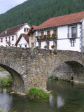 Village in the mountains. Typical houses, medieval stone bridge and river in Ochagavia, a little village in the north spanish mountains. Cloudy day Royalty Free Stock Images