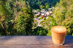 Village in mountains Mae Kampong Chiangmai Thailand. Coffee cup of hot Latte with blur background of Top view village in mountains Mae Kampong Village Chiangmai Stock Images