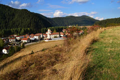 VILLAGE. IN THE MOUNTAINS AND SMALL CHURCH IN AUTUMN MEADOWS Royalty Free Stock Photos