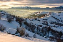 Village in mountains on winter sunrise. Beautiful landscape in Carpathians Stock Images
