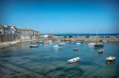 Landscape of Mousehole harbour Cornwall England. Village of Mousehole and boats in its clear blue waters Royalty Free Stock Photo